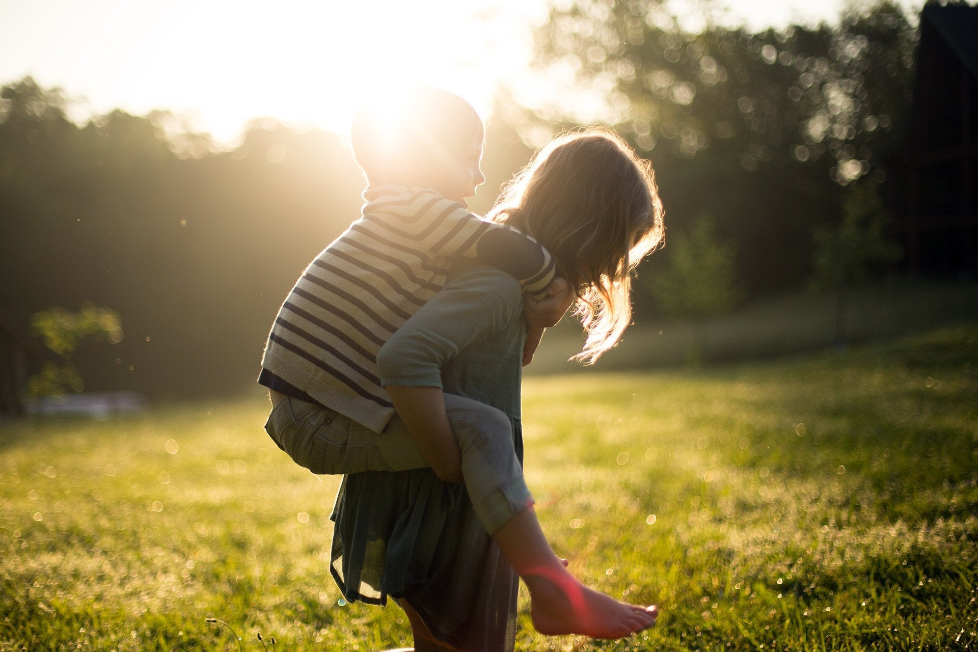 Sister giving Brother a piggyback ride at dawn in a field