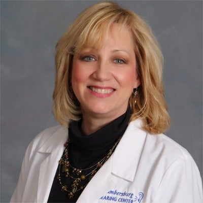 middle aged, blonde female wearing a white professional jacket sitting in front of a gray background